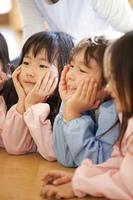 頬杖をついて微笑む幼稚園児