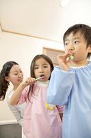 歯磨きをする幼稚園児と幼稚園教諭