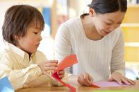 折り紙を折る保育士と保育園男児