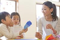 折り紙を折る保育士と保育園児
