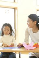 折り紙を折る保育士と保育園女児
