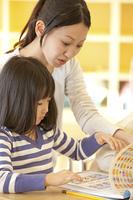 知育ドリルをする保育園女児と保育士
