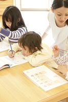 知育ドリルをする保育園児と保育士