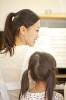保育士のピアノに集まる保育園女児