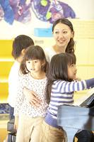 保育士のピアノに集まる保育園児