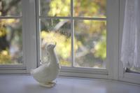 秋の白い窓辺と木製のアヒル