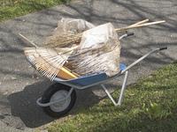 掃き掃除した後に一輪車でゴミを運ぶ