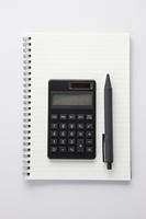 手帳の上に置かれたボールペンと電卓
