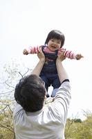 お父さんに抱き上げられる幼児