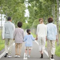 一本道で手をつなぐ3世代家族の後姿