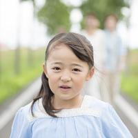 一本道で微笑む女の子と見守る家族