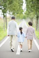 一本道で手をつなぐ祖父母と孫の後姿