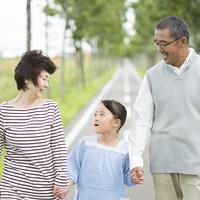 一本道で手をつなぐ祖父母と孫