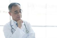 考え事をする医者