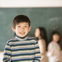 黒板の前で微笑む小学生の男の子