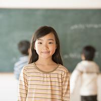 黒板の前で微笑む小学生の女の子