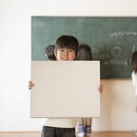 黒板の前でメッセージボードを持つ小学生の男の子