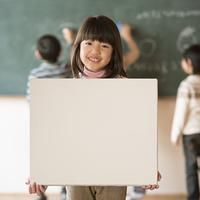 黒板の前でメッセージボードを持つ小学生の女の子