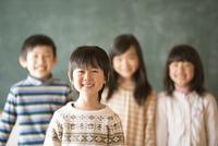 黒板の前で微笑む小学生