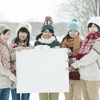 メッセージボードを持ち微笑む中学生