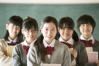 黒板の前で微笑む中学生