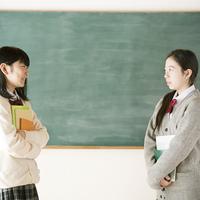 黒板の前で向き合う中学生