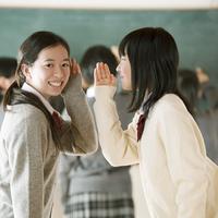 黒板の前で内緒話をする中学生