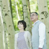 森林の中で微笑むシニア夫婦