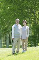 草原で微笑むシニア夫婦