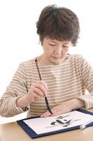 書道をするシニア女性