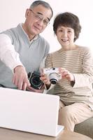 カメラを持ち微笑むシニア夫婦