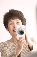 カメラで写真を撮るシニア女性