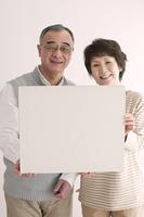 メッセージボードを持ち微笑むシニア夫婦