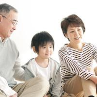 床に座り微笑む孫と祖父母