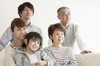 ソファーに座り微笑む3世代家族