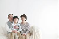 ソファーに座り微笑む孫と祖父母