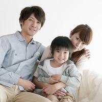 ソファーに座り微笑む家族