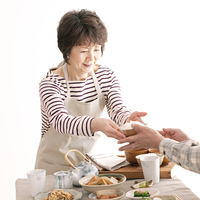 ご飯を手渡すシニア女性