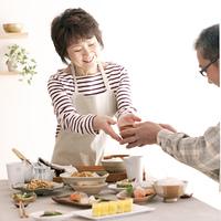 味噌汁を手渡すシニア女性