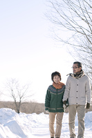 雪道を歩くシニア夫婦