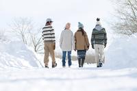 雪道を歩く若者たちの後姿