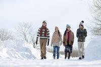 雪道を歩く若者たち