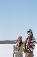 雪原でスコップを持ち微笑むカップル