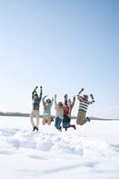 雪原でジャンプをする若者たち