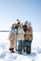 雪原で寒そうにする若者たち