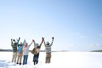 雪原で両手を挙げる若者たちの後姿
