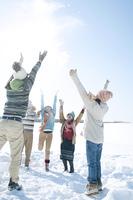 雪原で雪を舞い上げる若者たち