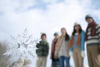 雪の結晶を持つ手元と若者たち