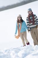 手をつなぎ雪原を歩くカップル