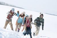 手をつなぎ雪原を歩く若者たち